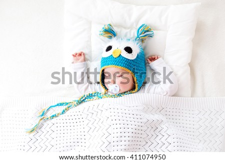 seven month old boy sleeping in the bed in owl hat - stock photo