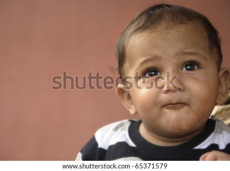 Seven month old indian orgin asian toddler looking up at the sky happily. - stock photo