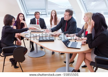 seven people having a business meeting in the conference room