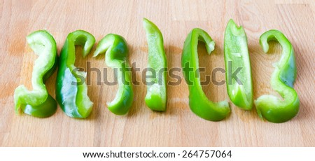 Seven pieces of sweet green pepper under a daylight on a wooden board - stock photo