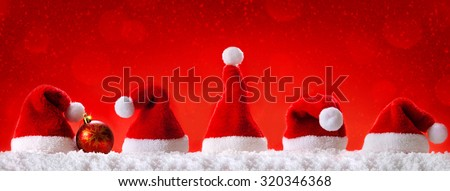 Seven red santa hats isolated on red background.Christmas  red background with Christmas hats.Red  Christmas hats. - stock photo