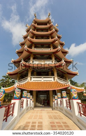 Seven Storey Chinese Pagoda over Ancient Traditional Bridge under Sunny Clear Blue Sky in Summer, Suphanburi, Thailand - stock photo