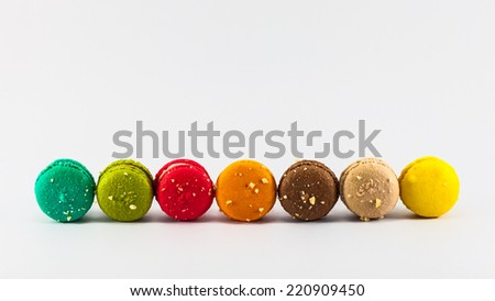 Seven sweet colorful french macaroons on white background