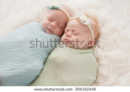 Seven week old fraternal, twin baby girls swaddled and sleeping on a white flokati rug. One sister is smiling. - stock photo