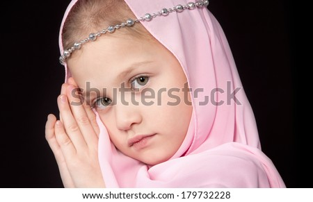 Seven year old blonde girl looking pensively in a pink scarf put her hands to the face on a black background - stock photo