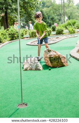 Seven year old boy playing miniature golf in the summer