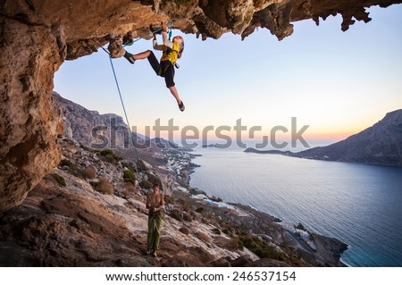 Seven-year old girl climbing a challenging route, father belaying - stock photo