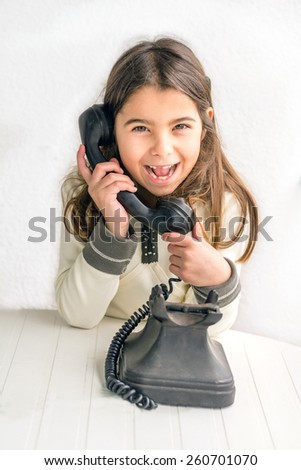 Seven year old girl with old vintage phone before white background - stock photo