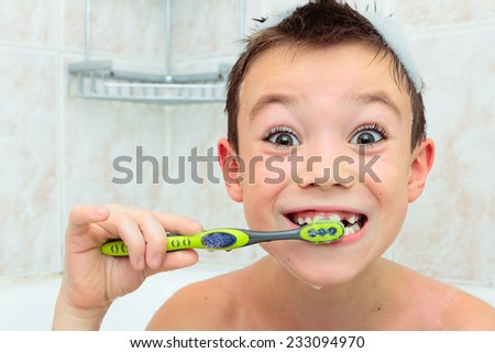 Seven years boy is brushing his teeth  - stock photo
