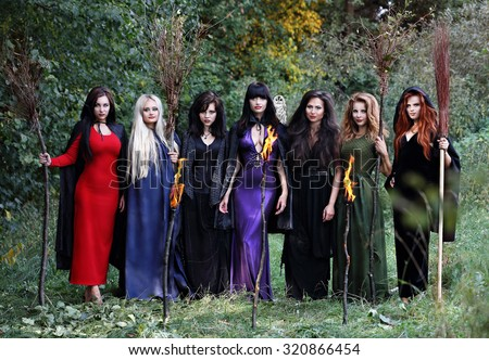 Seven young witches with brooms in the forest, standing in a row - stock photo