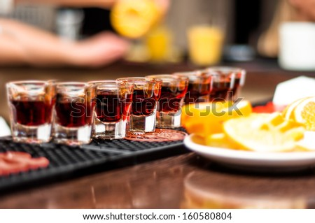 Several alcohol shots on bar with tequila and orange or lemon - stock photo