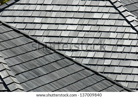 Several angled rooftops with worn and weathered wooden shingles - stock photo