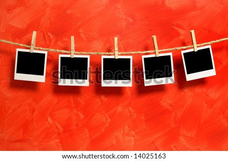 Several blank polaroid style instant camera photo prints hanging on a rope or washing line isolated against a red background.  Space for copy. - stock photo