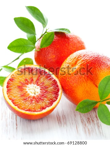 Several blood oranges with leaves,whole and halved on a wooden table - stock photo