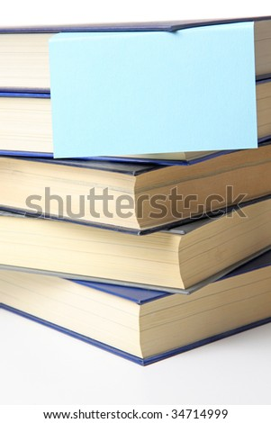 Several books lying one upon another. A notepad is attached. All on white background.