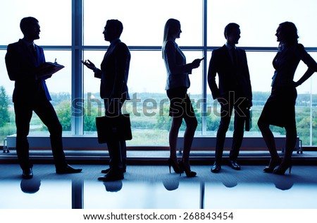 Several business partners communicating against window - stock photo