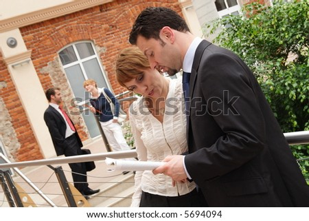 Several business people discussing outdoors. - stock photo