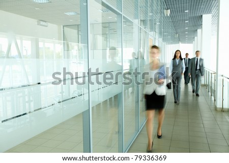 Several businesspeople walking in the corridor - stock photo