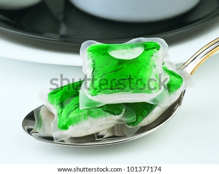 several capsules dishwasher soap with dish - stock photo