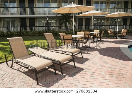 Several chairs with a parasol for sunbathing by the pool. - stock photo