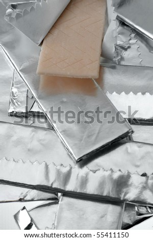 several chewing gums packed in wrapping foil, one open, detail vertical photo