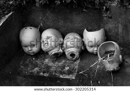 several children head doll with blue eyes lie in the old yard - scary stories - fear - a fairy tale - stock photo