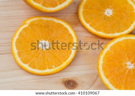 Several chopped orange slices lie on a wooden background