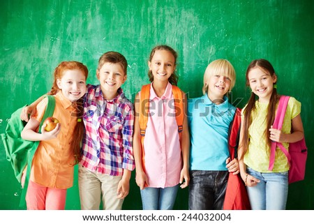 Several classmates with backpacks looking at camera - stock photo