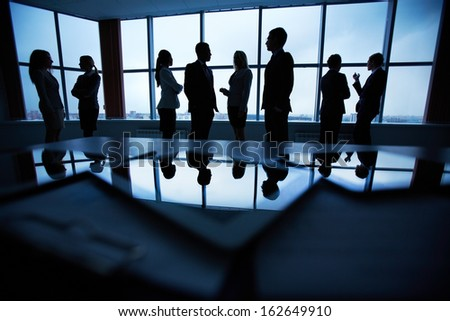 Several colleagues communicating in office against window