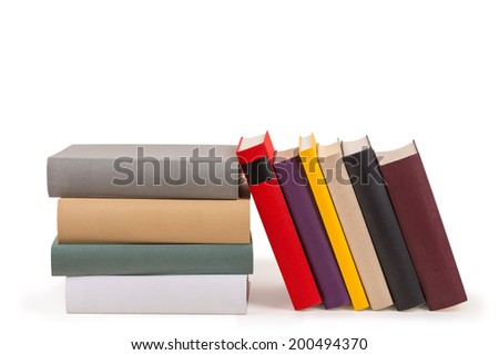 Several colored books in a row and a staple. - stock photo