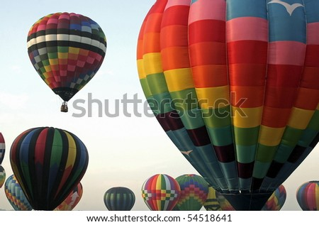 Several colorful hot air balloons inflated and ready for take off. - stock photo