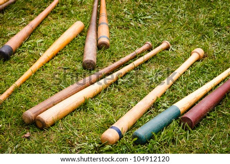 Several colorful old wooden vintage baseball bats are scattered on a green grass background - stock photo