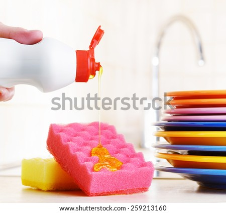 Several colorful plates, a kitchen sponges and a plastic bottle with natural dishwashing liquid soap in use for hand dishwashing. Eco-friendly, toxin-free, green cleaning product. Dishwashing concept. - stock photo