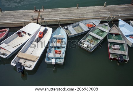 Several colorful, small boats tied to a simple wooden dock. - stock photo
