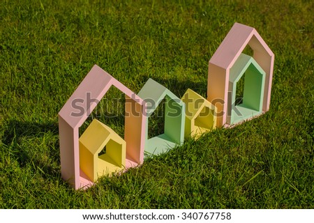 several colorful wooden houses on green grass - stock photo