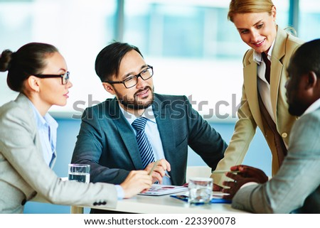Several confident businesspeople interacting at meeting - stock photo