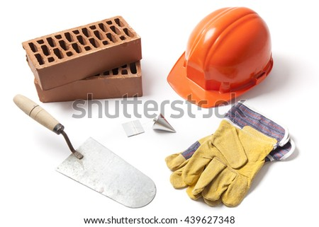 Several construction accessories trowel, bricks, plummet, hard hat and gloves isolated on white background. - stock photo