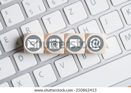 several contact options as icon on little cubes lying on a keyboard