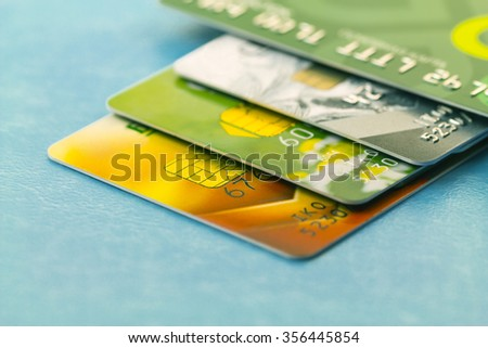 Several credit cards of different banks on light blue background. - stock photo
