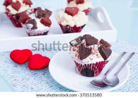 Several cupcakes for Saint Valentines day on white tray. Two red decorative hearts on table - stock photo