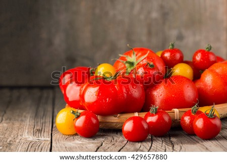 Several different fresh organic tomatoes on old rustic wooden background, selective focus - stock photo