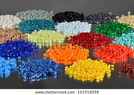 several dyed polymer resins for plastic industry on mirror - stock photo