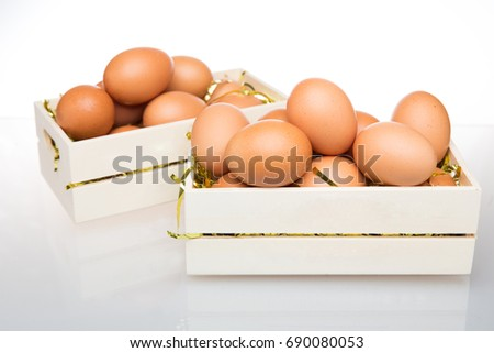 Several eggs, a wooden crate on a white background.