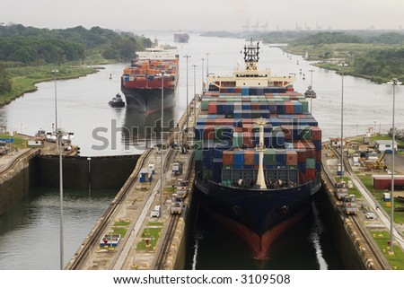 Several freighters, assisted by tugboats, are entering the Panama Canal at Gatun Locks on the Atlantic side. These container ships are fully loaded with cargo heading west towards the Pacific. - stock photo