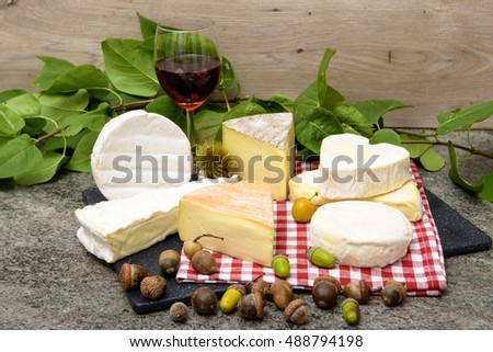 several french cheeses with a glass of red wine