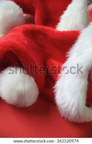Several furry Santa Claus hats on a red background with copy space - stock photo