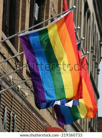 Several gay pride flags hanging from a building