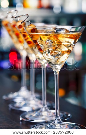 Several glasses of famous cocktail Martini, shot at a bar with shallow depth of field Ingredients: 55 ml gin, 15 ml dry vermouth, olives to garnish - stock photo