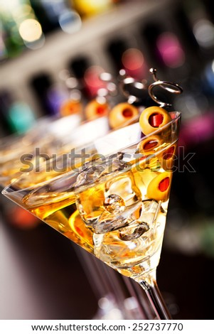 Several glasses of famous cocktail Martini, shot at a bar with shallow depth of field Ingredients: 55 ml gin 15 ml dry vermouth olives to garnish - stock photo