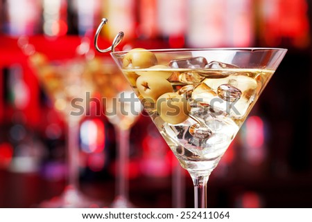 Several glasses of famous cocktail Martini, shot at a bar with shallow depth of field. The cocktail is made from 55 ml gin,15 ml dry vermouth,olives to garnish - stock photo